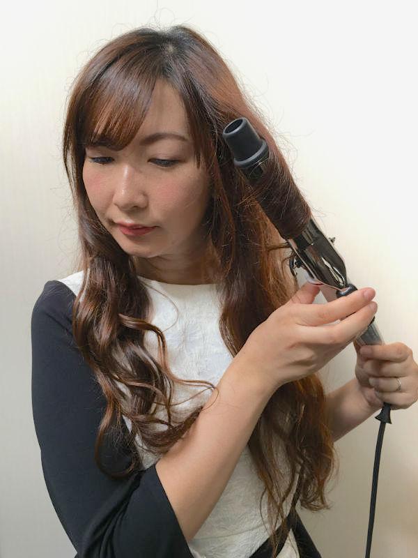 髪をヘアアイロンで巻くロングヘアの女性