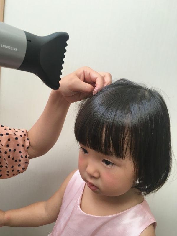 ドライヤーで髪を乾かしてもらう女の子