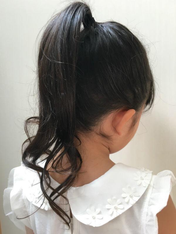 髪を頭頂部あたりで束ねた女の子