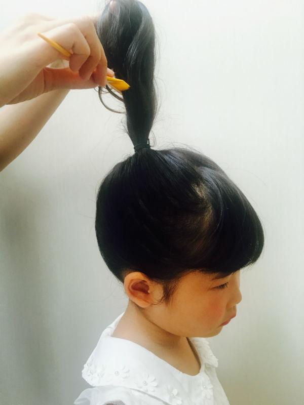 束ねた髪にクシで逆毛を立てる