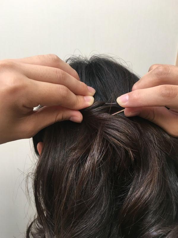 ねじった髪をヘアピンで後頭部に留める女性