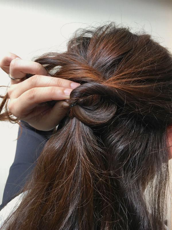 後ろの毛束を結び目の内側に回し入れる