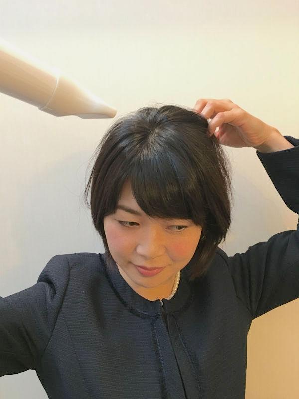 ドライヤーで髪を乾かすショートヘアの女性