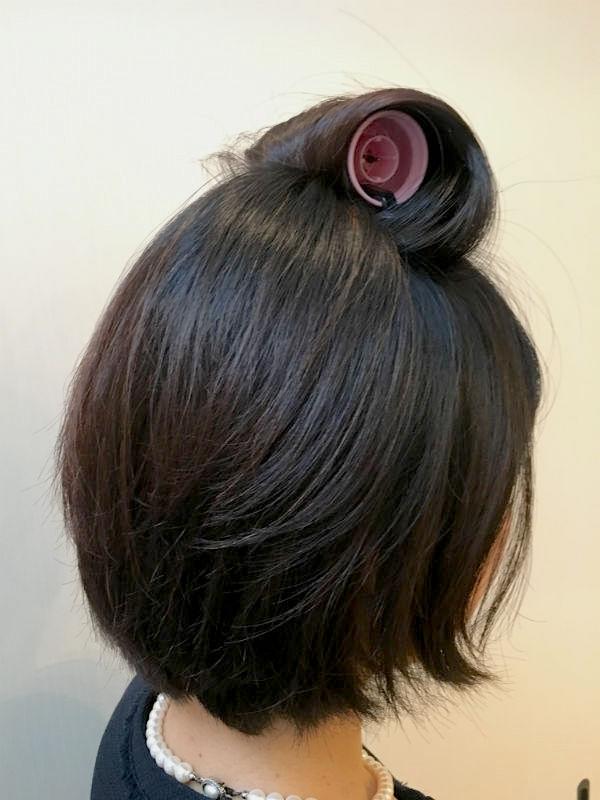カーラーで頭頂部の髪を巻く女性