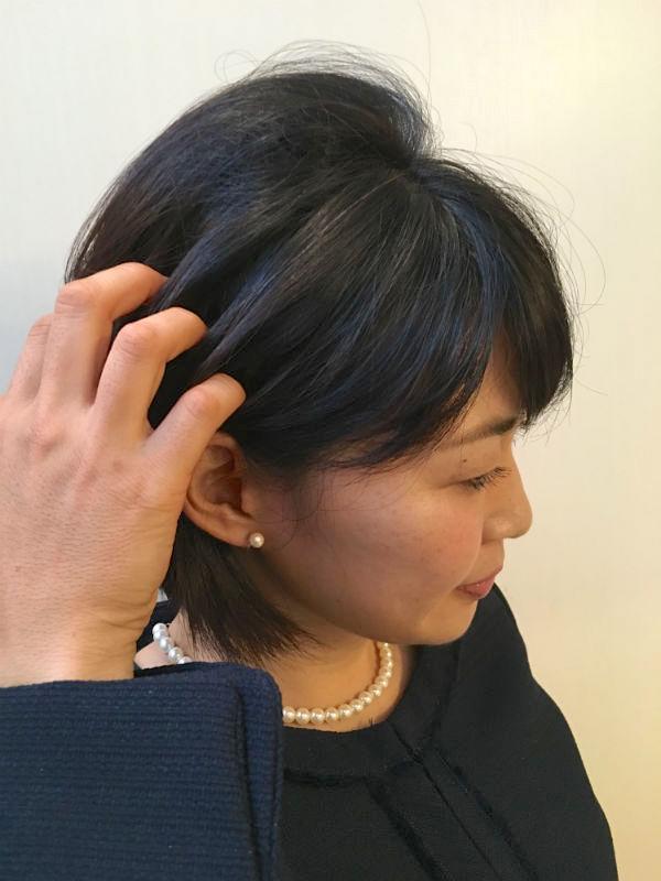 手で髪をとかすショートヘアの女性