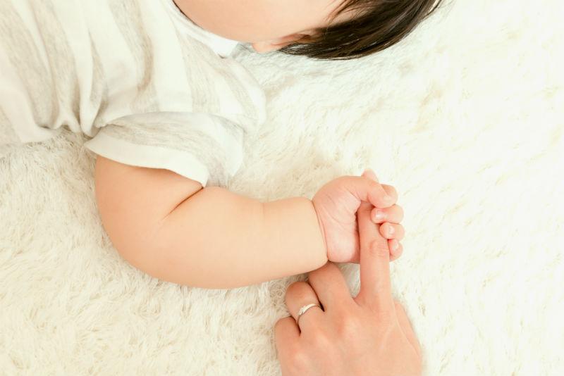 ママの指を握る赤ちゃん