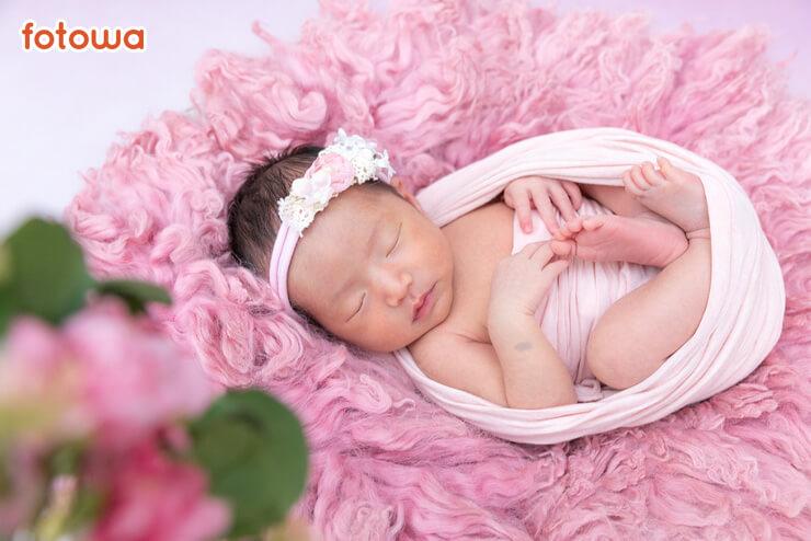 ニューボーン_ピンクのおくるみに包まれた赤ちゃん