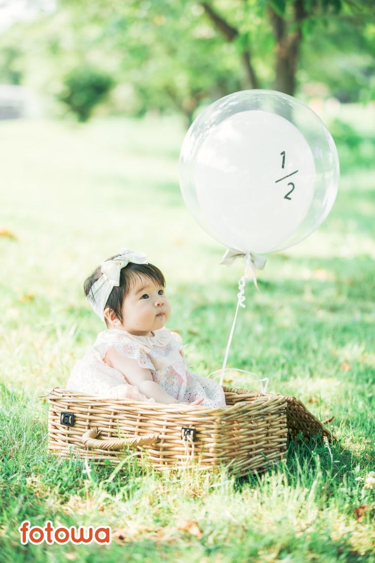 ハーフバースデーの撮影で風船を持って芝生に座りこむ赤ちゃん